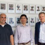 Bild von Prof. Jason Cong (m) mit Frank Hannig (l) und Prof. Teich vor der Galleriewand des Lehrstuhls