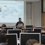 Bild im Praktikumsraum des Lehrstuhl mit Schülern im Vordergrund und Stefan Wildermann im Hintergrund vor einer Vorlesungsfolie
