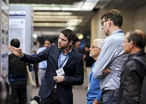 T. Schwarzer showing his poster to interested visitors of exhibition; Copyright: DATE 2019/copyright: Cruz Garcia