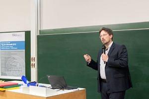 "Oliver Keszöcze talking and standing in front of his laptop during his lecture ""Entwurf von Mikrofluidischen Biochips"""