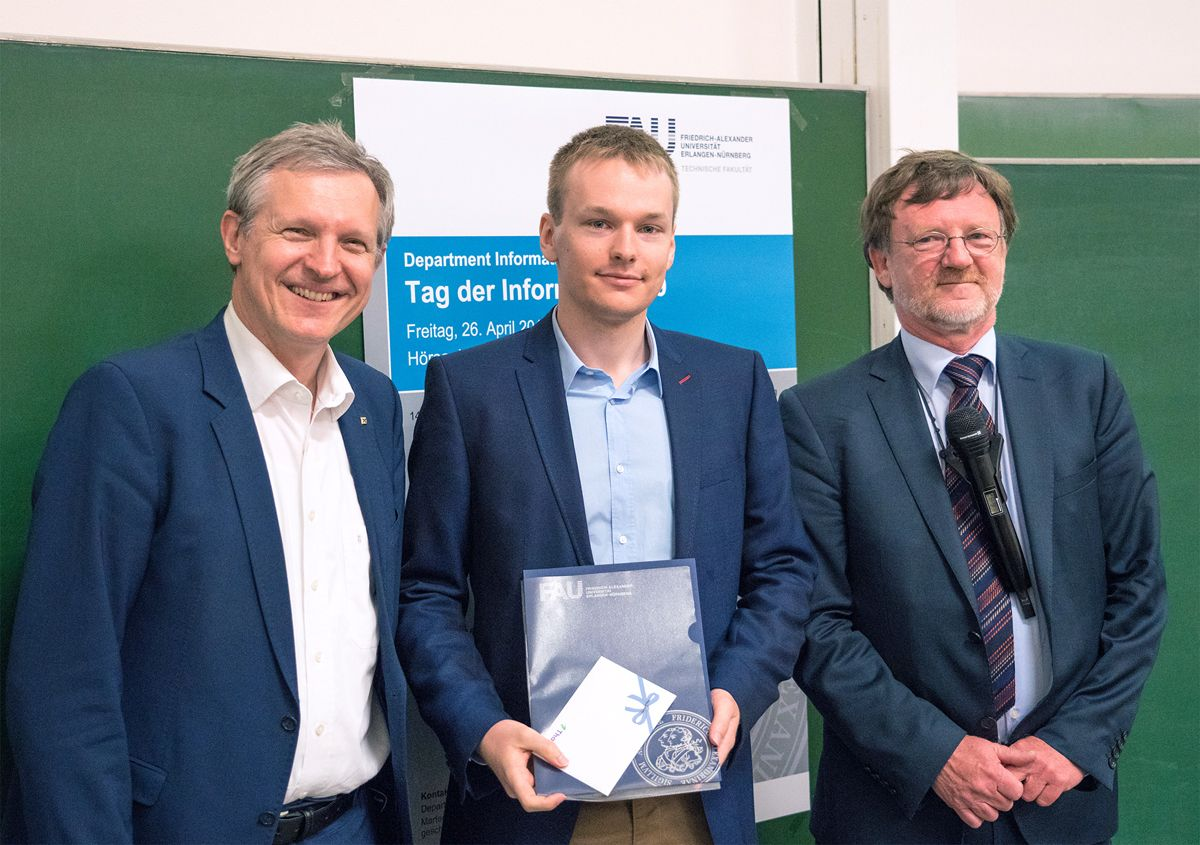 from the left: Prof. J. Teich, F. Wolff, (holding his award in hands) Prof. U. Rüde standing and smiling